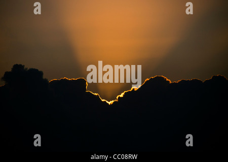 The golden rays of the setting sun create a golden lining to the edge of a cloud. Photo was taken at sunset on Swains - Stock Image