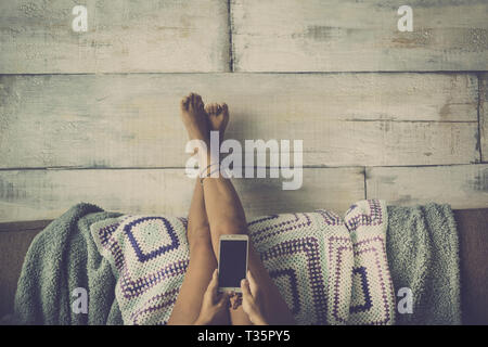 Woman lying on the couch with legs resting on the wall relaxed looking at the phone - concept of girl alone at home with technology - grey vintage col - Stock Image