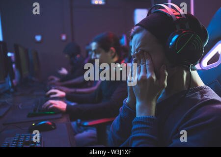 Young geek guy in headset rubbing eyes while feeling eye fatigue from computer monitor, he playing video game - Stock Image