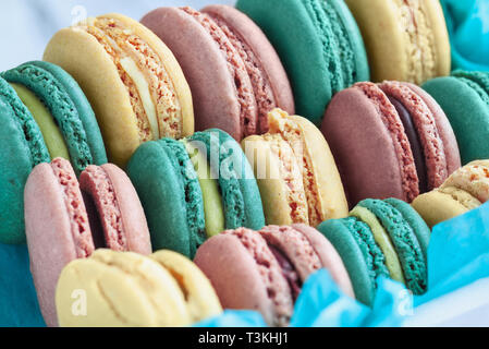 Assortment of fresh french macarons packaged in a pretty blue paper with blurred  background.. - Stock Image