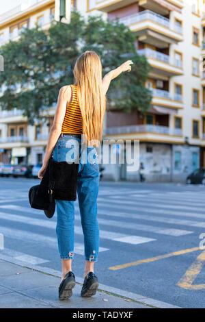Spain, teenage girl hailing a taxi - Stock Image