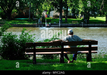 Retired man sitting on park bench next to river. - Stock Image