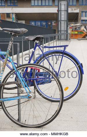 Two bicycles locked on metal racks in the city center of Poznan, Poland - Stock Image