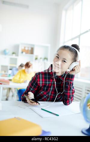 Cute little schoolgirl listening to her favorite music in headphones from playlist in smartphone - Stock Image