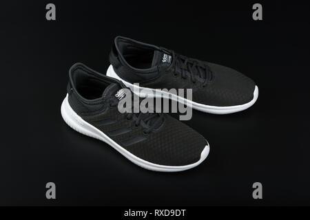BURGAS, BULGARIA - MARCH 8, 2019: Adidas Women's Essentials Cloudfoam QT Flex Shoes Black on black background. - Stock Image
