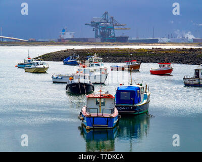 Fishing and pleasure boats in Paddys Hole Harbour, Teesmouth, Redcar Cleveland UK, with a bulk carrier ship at the Redcar Bulk Terminal - Stock Image