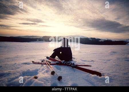 Rear view of skier sitting on snowy mountain against sky - Stock Image