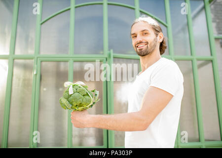 Man holding fresh bunch of broccoli tied in a bow as a gift outdoors on the green background - Stock Image