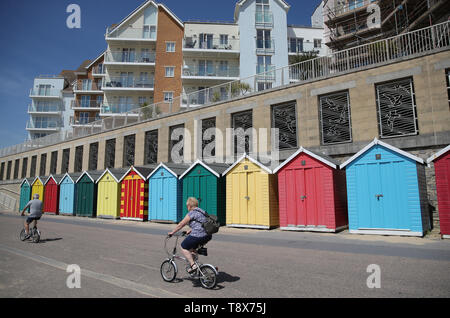 People make their way past beach huts on Boscombe beach as they enjoy the warm weather. - Stock Image