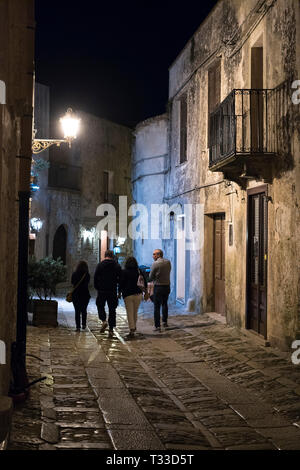 Tourists strolling on stone cobbles at night in cobbled street alleyway in Erice, Sicily, Italy - Stock Image