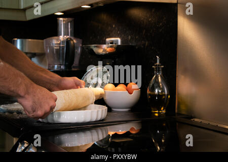 Arms of male chef using rolling pin to roll out pastry into a dish - Stock Image