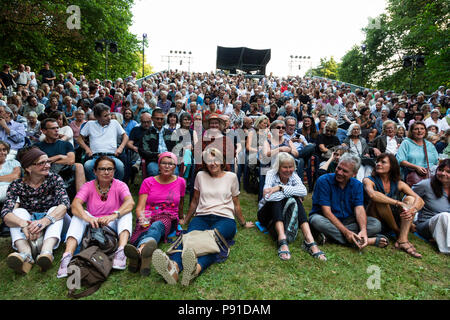 Mülheim an der Ruhr, Germany. 13 July 2018. A large audience watches The Art of Comedy by Eduardo de Filippo performed by Theater an der Ruhr during the Weiße Nächte 2018 season, a series of free open-air performances at Raffelbergpark. Photo: Bettina Strenske/Alamy Live News - Stock Image