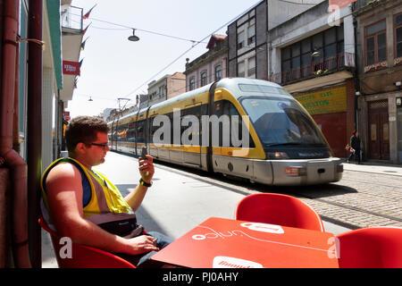Por176Portugal, Porto, Matosinhos, Rua de Brita Capelo, suburban light rail train passing pavement café - Stock Image