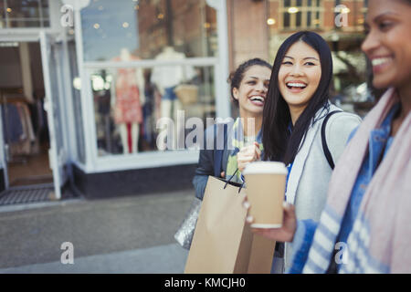 Laughing women friends walking along storefront with coffee and shopping bags - Stock Image