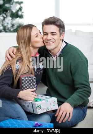 Woman With Christmas Gifts Kissing Man On Cheek - Stock Image