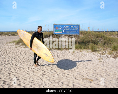 Wrightsville beach, Wilmington, North Carolina, NC. A surfer walks past an information sign. - Stock Image