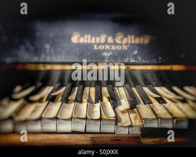 Old worn and broken piano - Stock Image