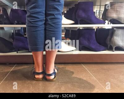 A low angle view of a girl wearing sandals in a shoe shop whilst looking at rows of boots and shoes for sale - Stock Image