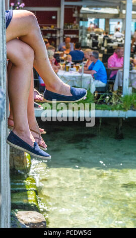 Female legs dangling over a wall with customers eating at a outdoor restaurant in Malcesine on the shore of Lake garda. - Stock Image