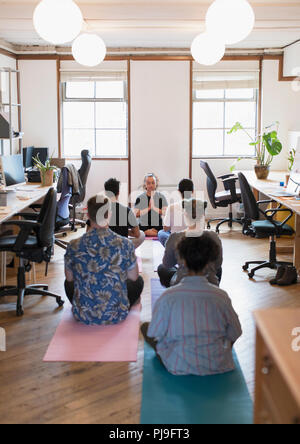 Creative business people meditating in office - Stock Image