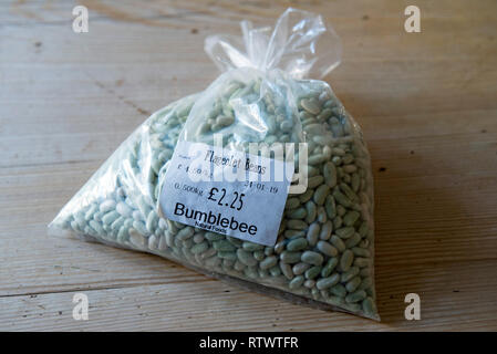 Bag of Flageolet Beans with shop label in half light on wooden kitchen table. - Stock Image