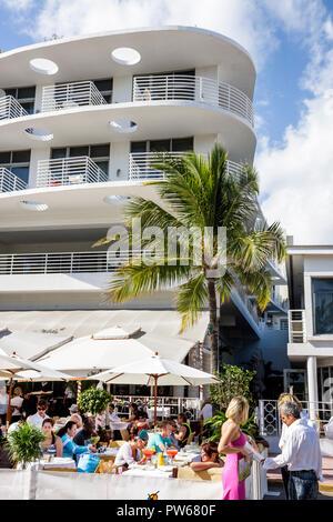Miami Beach Florida Ocean Drive New Year's Day Art Deco District sidewalk cafe restaurant business umbrellas alfresco al fresc - Stock Image