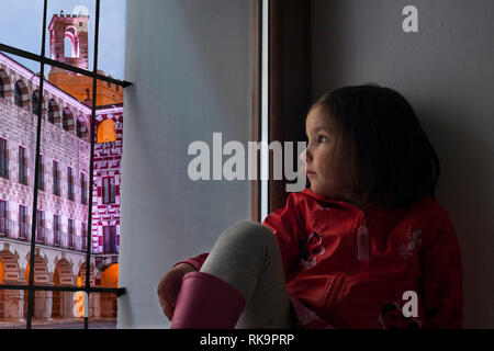 Little girl observing the Badajoz Plaza Alta sitting in her home sill. She is wearing raincoat - Stock Image
