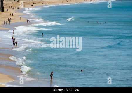 People of multi generation families enjoying seaside recreation and pass-time on beach - Stock Image