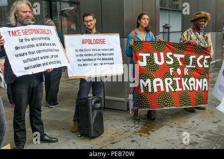 London, UK. 13th August 2018. Protesters outside the offices of BASF. Three days before the 6th anniversary of the massacre when 34 striking miners were shot dead by South African police at Lonmin's Marikana platinum mine, a tour of the City of London visited investors, insurers and shareholders profiting from the violence against people and nature in Marikana and heard about the colonial roots of the huge wealth of the City. Credit: Peter Marshall/Alamy Live News - Stock Image