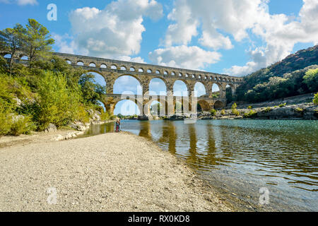 A couple stand on the beach at a riverbank of the Gardon River in Provence, France with the ancient Roman aqueduct Pont du Gard in the background - Stock Image