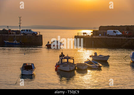 Mousehole, Cornwall, UK. 20th Apr, 2019. UK Weather. The hot Easter weekend weather looks to continue in Cornwall today, as a small fishing boat heads out of the harbour at sunrise. Credit: Simon Maycock/Alamy Live News - Stock Image