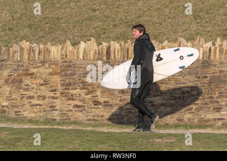 A surfer carrying his surfboard and walking along a footpath. - Stock Image