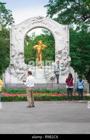 Vienna tourism, tourists visit the famous gold statue of Johann Strauss in the Stadtpark in Vienna, Austria. - Stock Image