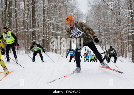 Competitors climb a hill on the trail between Cable and Hayward, Wisconsin during the American Birkebeiner on February - Stock Image