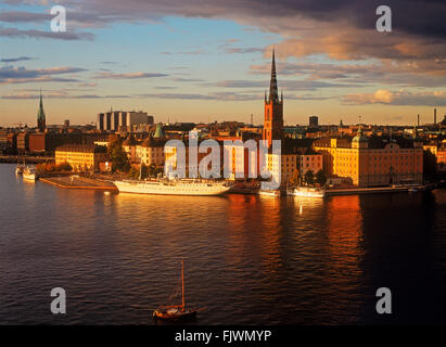 Steeple of Riddarholmen Chruch on Riddarholmen Island reflecting off Riddarfjarden waters in Stockholm near sunset - Stock Image