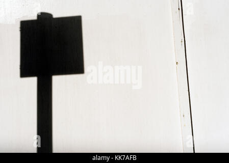 Blank black road sign silhouette with a white wood background and copy space area for rad safety ideas and concepts - Stock Image