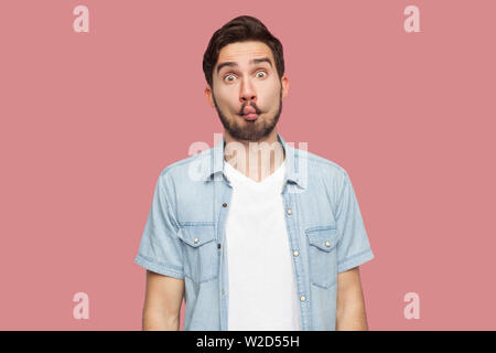 Portrait of funny comic face handsome bearded young man in blue casual style shirt standing with fish lips and looking at camera. indoor studio shot, - Stock Image