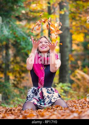 Nature-lover teen girl countrygirl throwing Autumn leaves in air upwards happy joyful smiling looking up - Stock Image