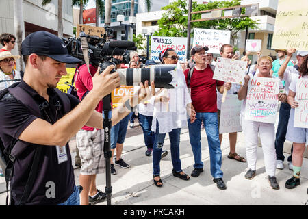 Miami Florida demonstration demonstrating protest protesting Families Belong Together Free Children illegal immigration media videocam Mexican border - Stock Image