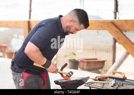 Blacksmith working on the anvil, making a horseshoe . - Stock Image