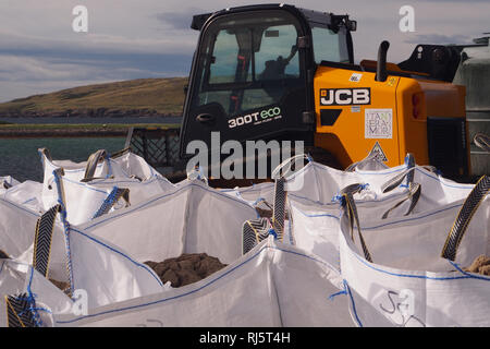 A JCB 300T ECO skid loader, used for heavy lifting, with a group of white filled hippo bags in front of the vehicle and the sea and an island behind - Stock Image