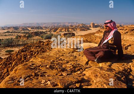Saudi Arabia, Madinah, nr. Al-Ula, Madain Saleh (aka Hegra). A Saudi man gazes at stark cliffs and rocky outcrops - Stock Image