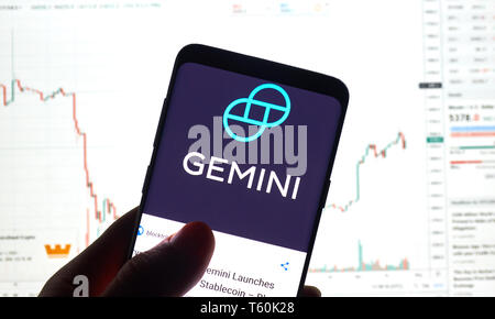 MONTREAL, CANADA - APRIL 26, 2019: Gemini cryptocurrency exchange logo and application on Android Samsung Galaxy s9 Plus screen in a hand over a lapto - Stock Image