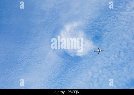 Southeast London, UK, 10th July 2018. A twirled UFO shaped cloud can be seen above Southeast London as a plane flies by. The dark grey clouds that dominated the skies earlier in the day have cleared and the brighter conditions have created some interesting cloud formations. Credit: Imageplotter News and Sports/Alamy Live News - Stock Image