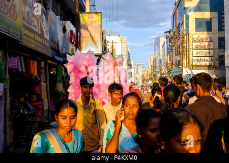 Two cotton candy sellers walk amidst the crowd on Netaji Subhas Chandra Bose Road, Tiruchirappalli (Trichy), Tamil Nadu, India. - Stock Image