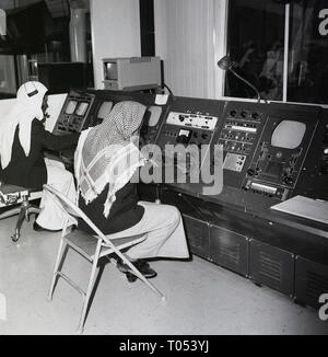 1960s, arab men in traditional dress working in a control room of a television studio, Saudi Arabia. - Stock Image