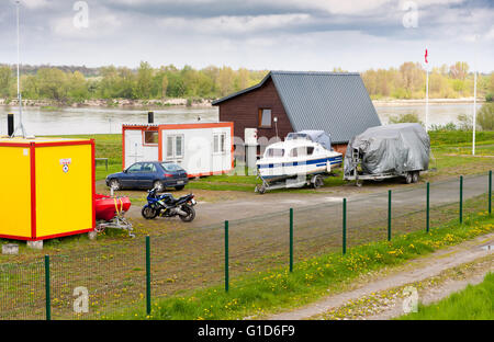 Parking in Kazimierz Dolny by the Vistula River, Poland, Europe, car, motor and sailing boat parked on the grassy - Stock Image