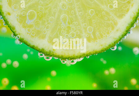 Closeup of the texture of sliced lime in the water with bubbles - Stock Image