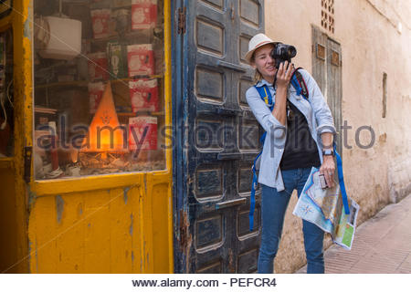 Young female tourist take photographs in Essaouira, Morocco. - Stock Image