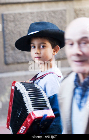 Old man passing in front of a very young boy busker with an accordion in Buenos Aires - Stock Image